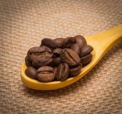 咖啡粒堆与木匙子的在黄麻 免版税库存照片