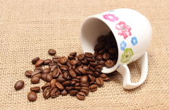 咖啡粒堆与被翻转的杯子的 免版税库存照片