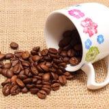 咖啡粒堆与被翻转的杯子的 库存照片
