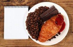 咖啡粒巧克力块和新月形面包在白色板材 免版税图库摄影