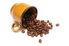 咖啡粒被翻转的杯子和堆在白色背景的 免版税图库摄影