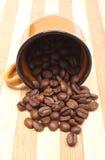 咖啡粒被翻转的杯子和堆  库存图片