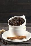 咖啡粒,糖,在木背景的桂香 免版税库存图片
