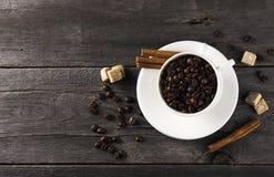 咖啡粒,糖,在黑暗的木背景的桂香 免版税库存照片