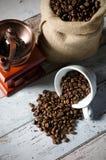 咖啡粒从杯子溢出 黄麻袋子烤豆和米尔 图库摄影