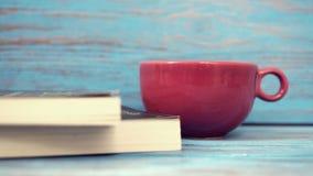 咖啡红色杯子&书在木桌上 库存照片