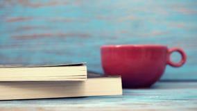 咖啡红色杯子&书在木桌上 库存图片