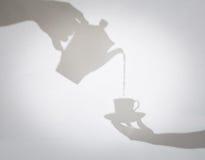 咖啡罐倾吐的咖啡的精美阴影到杯子里举行了  免版税库存图片