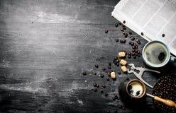 咖啡罐和一张报纸用烤咖啡豆 免版税库存图片