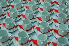 咖啡茶杯许多行有茶匙和一个红色盘的 白色和红色背景 库存图片