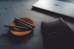 咖啡茶碟、豪华笔、膝上型计算机和笔记本在具体桌上 免版税库存照片