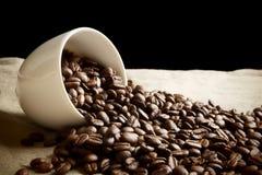 咖啡被撒布的豆从一个杯子的在黑色和胡麻 免版税图库摄影