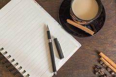 咖啡豆、咖啡,秋叶、笔和笔记本在木甲板 免版税库存图片