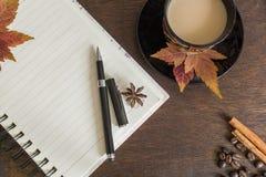 咖啡豆、咖啡,秋叶、笔和笔记本在木甲板 库存图片