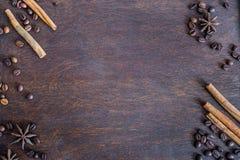 咖啡豆、桂香和茴香星在黑暗的木backround 免版税库存照片