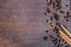 咖啡豆、桂香和茴香星在黑暗的木backround 免版税库存图片
