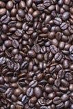 从咖啡豆上射击在桌上的 垂直接近的射击 免版税库存图片