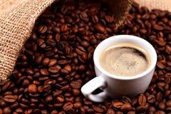 咖啡豆和一个杯子在粗麻布大袋 库存图片