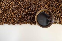 咖啡豆和咖啡在一个杯子有拷贝空间的 免版税图库摄影