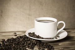 咖啡豆和咖啡在白色杯子在木桌上在a对面 免版税库存图片