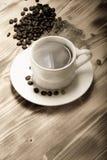 咖啡豆和咖啡在白色杯子在木桌上 有选择性 免版税库存照片