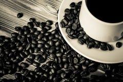 咖啡豆和咖啡在白色杯子在木桌上backgro的 免版税库存图片