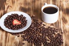 咖啡豆和咖啡在白色杯子在木桌上backgro的 库存照片