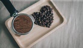 从咖啡豆和咖啡壶的心脏在桌面上准备了 免版税库存照片