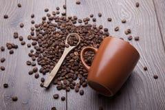 咖啡豆和咖啡杯木表面上 库存图片