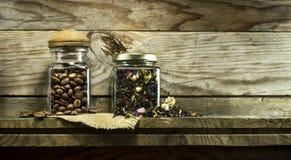 咖啡豆和干茶在玻璃瓶子 库存图片
