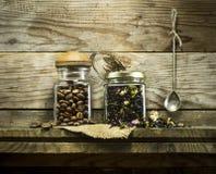 咖啡豆和干茶在玻璃瓶子 库存照片