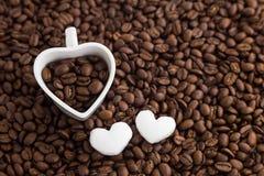 咖啡豆和心脏塑造在咖啡豆背景的杯子 对情人节 免版税库存图片