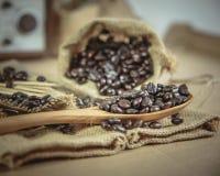咖啡豆和木匙子在大袋浮出水面 库存图片