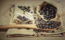 咖啡豆和木匙子大袋表面上, 免版税库存照片