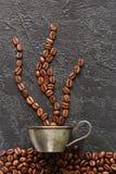 咖啡豆和杯子在灰色具体背景 库存照片