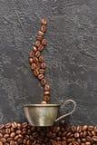 咖啡豆和杯子在灰色具体背景 免版税库存图片