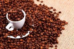 咖啡豆和杯子在粗麻布 免版税库存照片