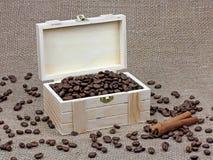 咖啡豆和桂香在一个木箱在帆布 免版税库存照片