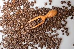 咖啡豆和橄榄色的木瓢在白色背景 免版税库存照片