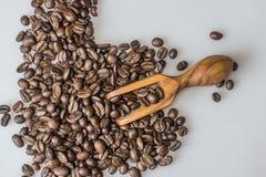 咖啡豆和橄榄色的木瓢在白色背景 库存图片