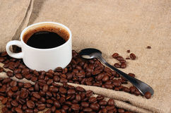咖啡豆和茶匙与一杯咖啡的碾碎的咖啡 免版税库存照片