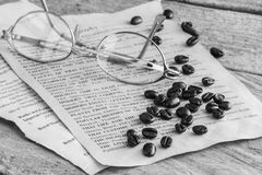 咖啡豆和玻璃在纸,黑白 免版税库存照片