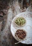 咖啡豆和绿色豆蔻果实在年迈的木头 图库摄影