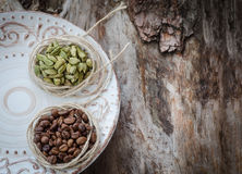 咖啡豆和绿色豆蔻果实在年迈的木头 库存图片