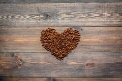 咖啡豆在心脏在黑暗的木台式视图copyspace塑造 背景咖啡准备好的使用 库存照片