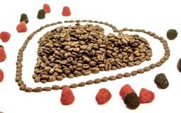 咖啡豆在心脏塑造与线在心脏附近用胶粘的糖果 免版税库存照片