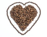 咖啡豆在心脏塑造与线在白色背景的心脏附近 免版税库存照片