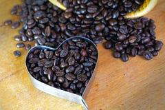 咖啡豆在木桌上的心脏形状 图库摄影