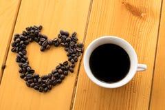 咖啡豆在木桌上的爱杯子 库存照片
