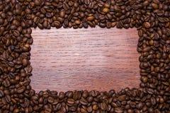咖啡豆在木头的框架背景 免版税库存照片